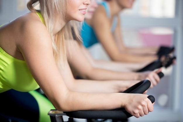 Groep vrouwen die fietsen met cardio training doen