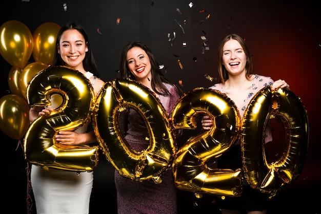 Groep vrouwen die met gouden ballons bij nieuwe jarenpartij stellen