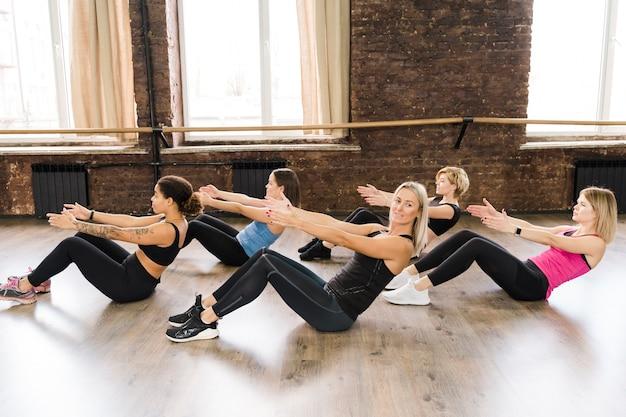 Groep vrouwen die samen bij de gymnastiek uitwerken