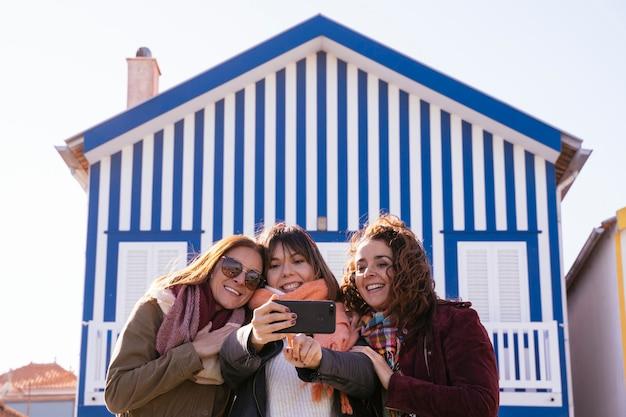 Groep vrouwen die selfie nemen bij blauw gestreept huis, het dorpshuis van de traditionele visser.