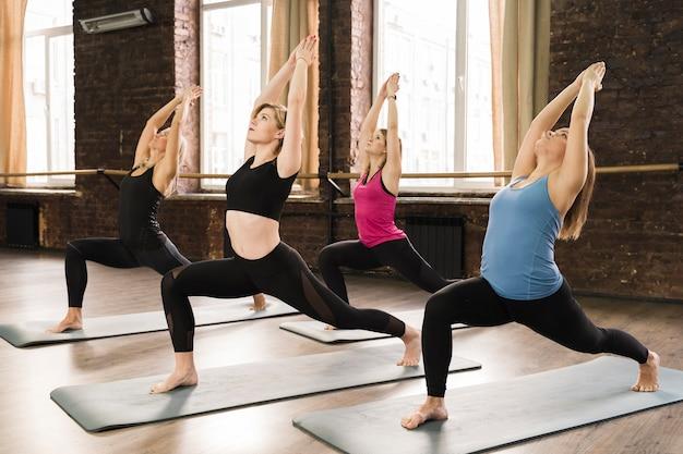 Groep vrouwen die zich bij de gymnastiek uitrekken