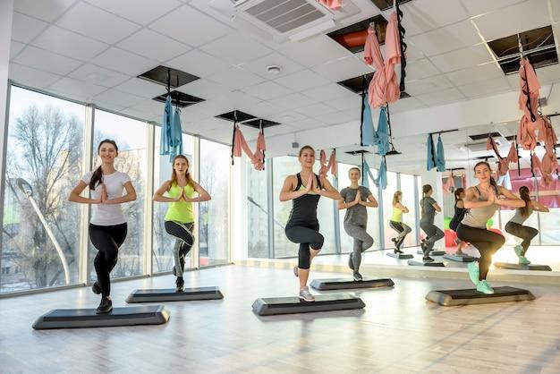 Groep vrouwen in de sportschool die evenwichtsoefeningen maken