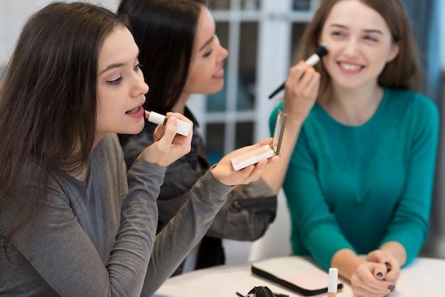 Groep vrouwen met make-upborstel en lippenstift