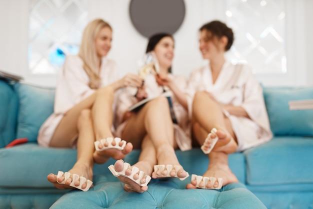 Groep vrouwen ontspannen op pedicure procedure in de schoonheidssalon.