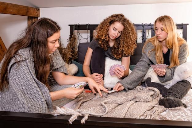 Groep vrouwen thuis die kaartspellen speelt, mensen die plezier hebben tijdens het spelen van bordspel