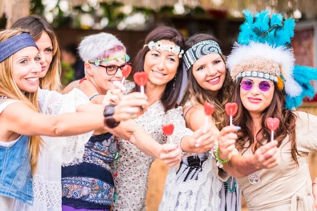 Groep vrouwen van verschillende leeftijden, van jong tot oud, blijven samen in vriendschap en nemen je een lolly met een snoepvuurplaats aan. vredig en levensstijl geïnspireerd op vrede en liefde zoals hippie-stijlpy