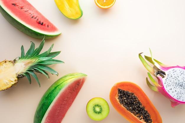 Groep vruchten op pastel achtergrond met schelpen.