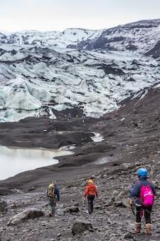 Groep wandelaars die aan gletsjer met gids lopen