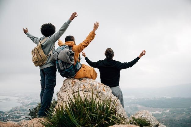 Groep wandelaars die bovenop bergpiek zitten die hun handen uitrekken