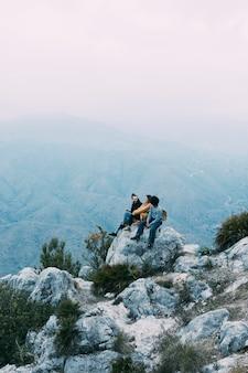 Groep wandelaars die op rots zitten