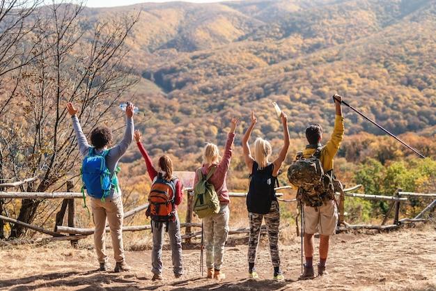 Groep wandelaars genieten van uitzicht. handen omhoog, rug omgedraaid. herfst tijd.
