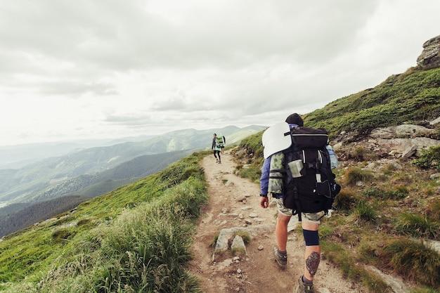 Groep wandelaars met rugzakken lopen langs een pad naar een bergrug