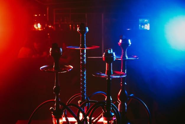 Groep waterpijpen met shisha-kolen in kommen op rode en blauwe lichten met rook