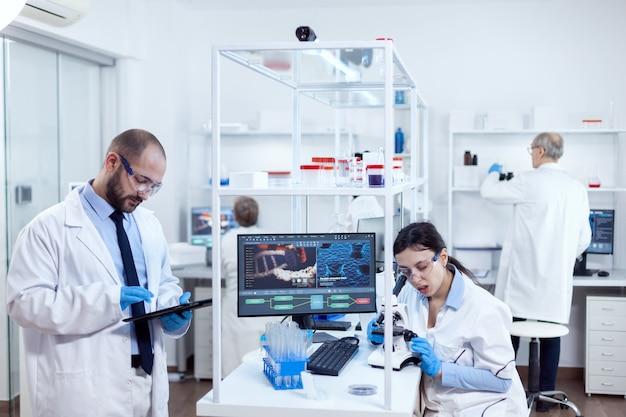 Groep wetenschappers die gezondheidsstudie doen met behulp van microscoop en tablet-pc. team van onderzoekers die farmacologie-engineering doen in een steriel laboratorium voor de gezondheidszorg met een afrikaanse assistent op de achtergrond