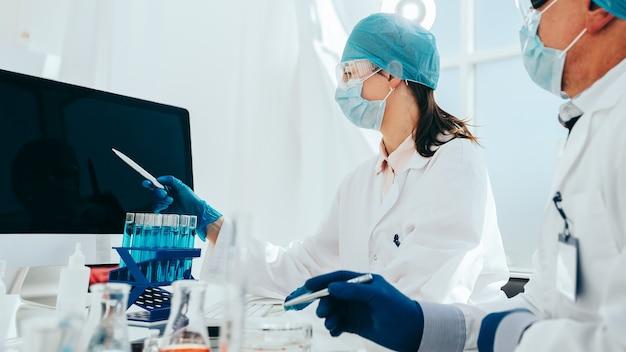 Groep wetenschappers kijken naar een computerscherm in het laboratorium