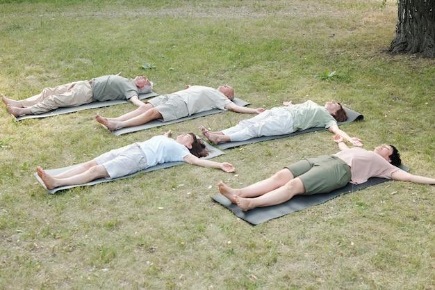 Groep yogastudenten die in lijkhouding liggen