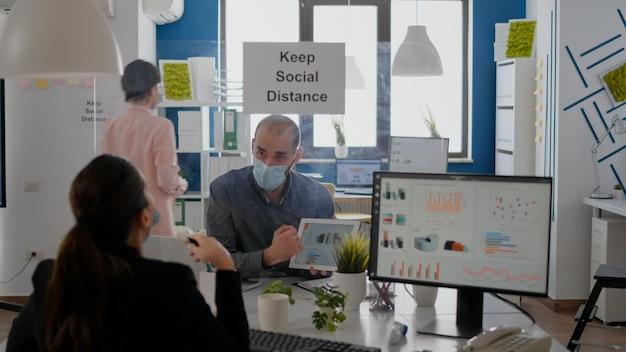 Groep zakelijke collega's met gezichtsmaskers die grafieken analyseren met behulp van digitale tablet die op een nieuwe normale werkplek zit. collega die op de achtergrond werkt, handhaaft sociale afstand