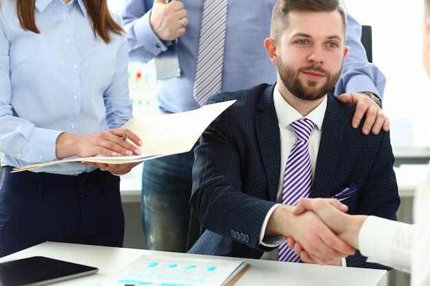Groep zakenlieden die handen na productieve vergadering schudden