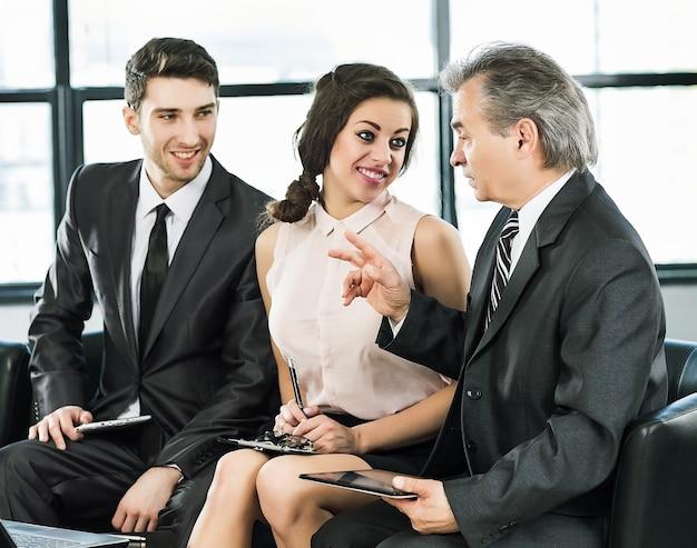Groep zakenlieden die het beleid van het bedrijf het bureau bespreken.