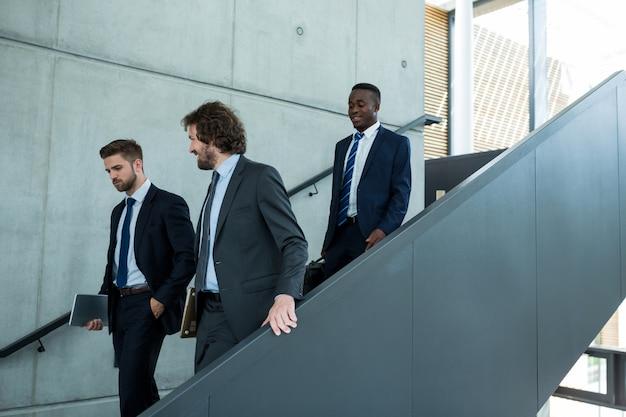 Groep zakenlieden die onderaan treden beklimmen