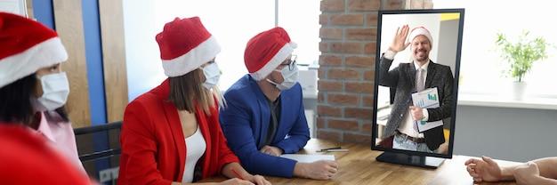 Groep zakenlieden en -vrouwen in beschermende gezichtsmaskers en santahoeden zitten aan tafel en