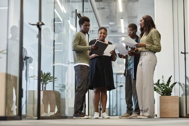 Groep zakenlieden en zakenvrouwen die briefing hebben in de kantoorgang wanneer ze met gedrukte...
