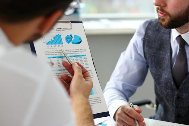 Groep zakenlieden met financiële grafiek en zilveren pen