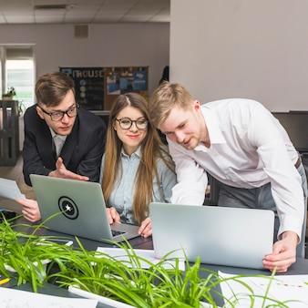 Groep zakenlui die aan laptop in bureau werken