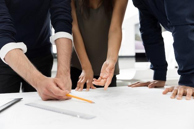 Groep zakenlui die bij een lijst in het bureau werken