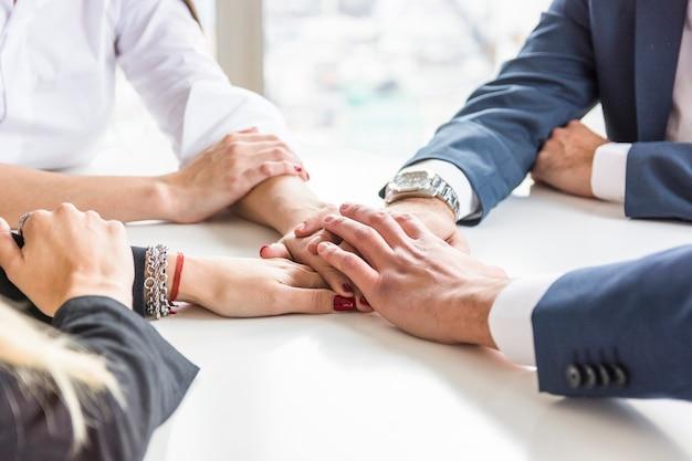 Groep zakenlui die elkaars hand op wit bureau stapelen