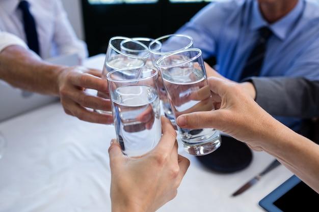 Groep zakenlui die glas water in restaurant roosteren