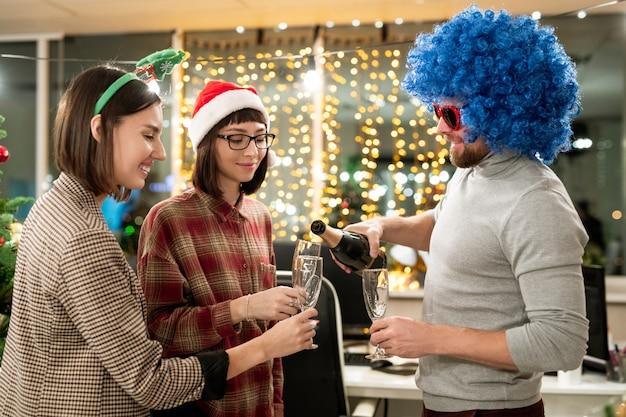 Groep zakenlui die kerstmis in bureau vieren en champagne gaan hebben voor de vakantie