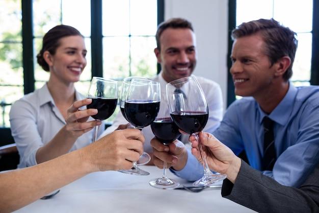 Groep zakenlui die wijnglas roosteren tijdens bedrijfslunchvergadering