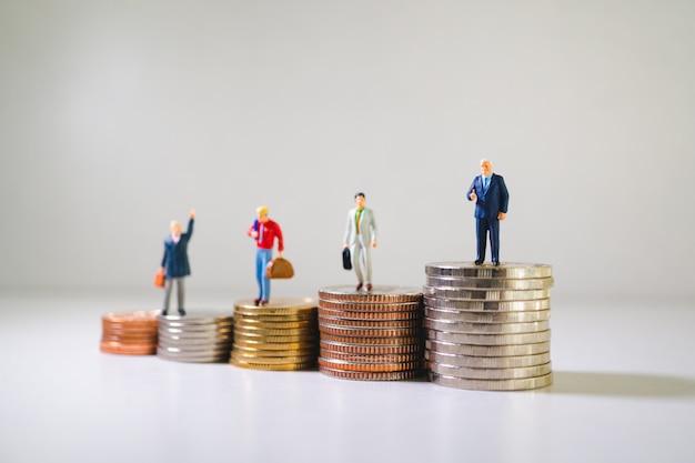 Groep zakenlui die zich op stapel muntstukken bevinden