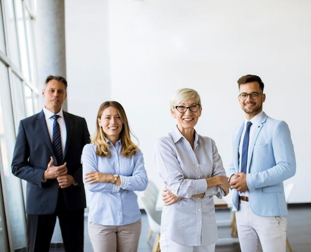 Groep zakenlui staan samen in het kantoor met hun volwassen vrouwelijke bedrijfsleider