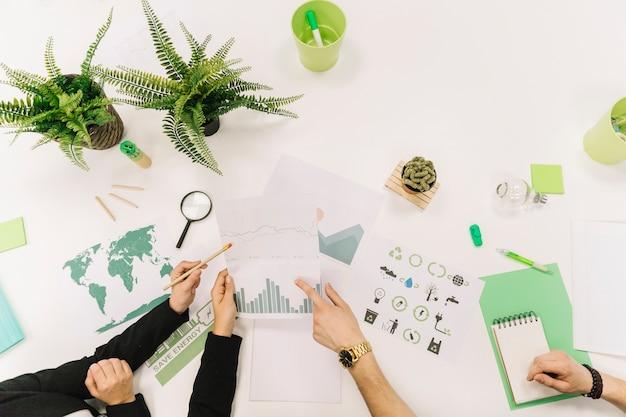 Groep zakenluihand die aan grafiek over witte achtergrond werken