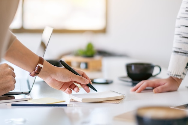 Groep zakenman bespreken en schrijven op notebook op tafel in kantoor