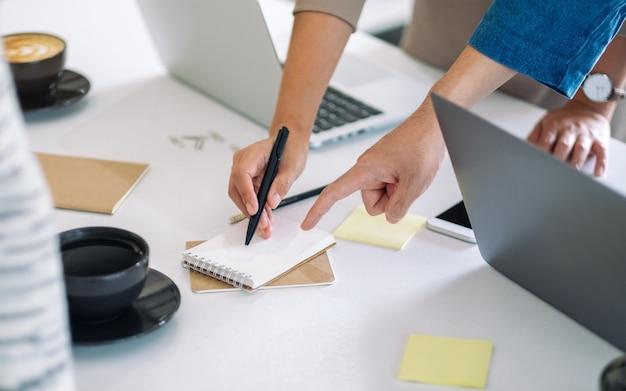 Groep zakenman bespreken, schrijven en wijzende vinger naar notebook op tafel in kantoor