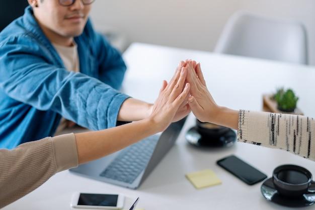 Groep zakenman die hun handen in elkaar steekt in de meeting