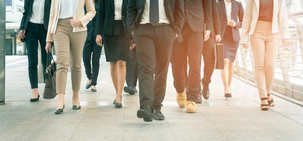 Groep zakenman en onderneemster die in moderne stad lopen