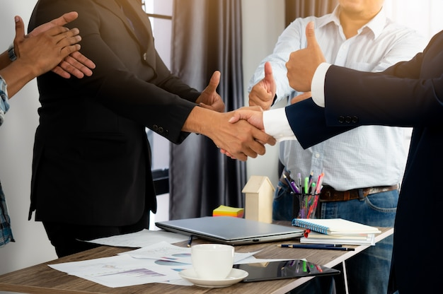 Groep zakenman vergadering en hand schudden na succesvol onderhandelen.