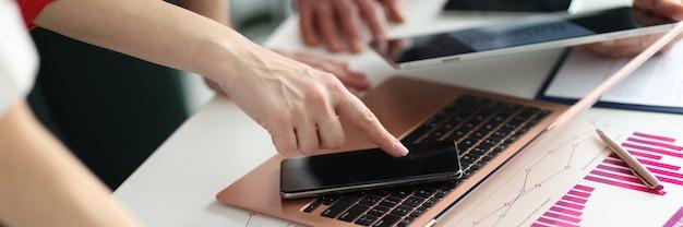 Groep zakenmensen die grafieken bestuderen in documenten en op gadgets business analytics concept