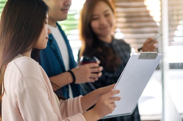 Groep zakenmensen die ideeën over whiteboard op kantoor bekijken en bespreken