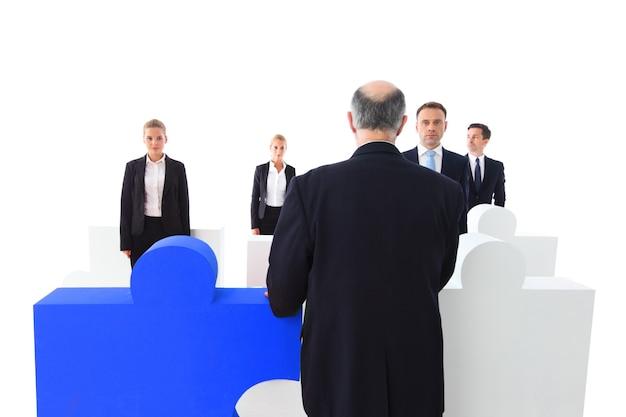 Groep zakenmensen die puzzel samenstellen die op witte achtergrond wordt geïsoleerd