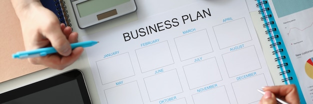 Groep zakenmensen die werkvergadering houden aan tafel met papieren documenten die jaarlijkse...