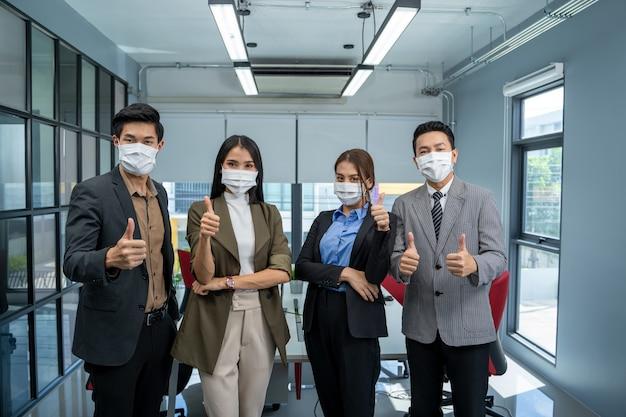 Groep zakenmensen dragen masker ter bescherming van covid-19 hebben een vergadering en praten op kantoor.