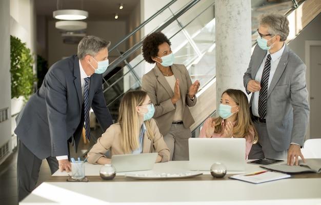 Groep zakenmensen hebben een vergadering en werken op kantoor en dragen maskers als bescherming tegen coronavirus