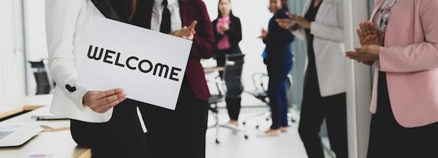 Groep zakenmensen voegt zich bij elkaar om welkomswoorden te begroeten en vast te houden voor een teken van geluk en plezier voor het komen van iets of iemand. goed teamwork in kantoorconcept.