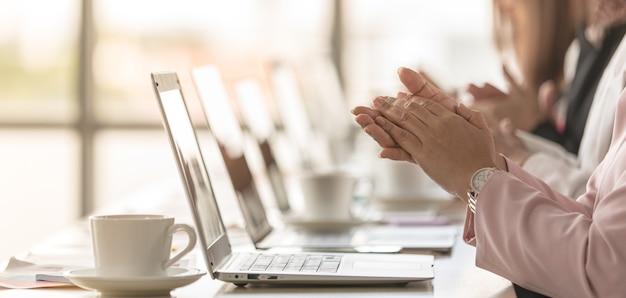 Groep zakenvrouwen die aan het bureau zitten en werken, de manager kijkt naar het laptopscherm en ziet succesnieuws en laat het anderen weten, dan klappen ze in de handen, glimlachen en lachen ze blij.