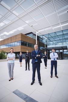 Groep zeker zakenlui die zich buiten de bureaubouw bevinden